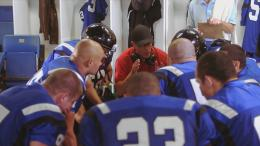 Football players kneeling around their coach