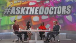 "The Doctors in front of screen that says ""#ASKTHEDOCTORS"""