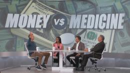hosts on stage with money vs. medicine on monitor behind them.