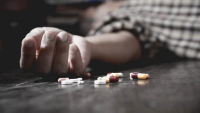 Person on the floor next to pills