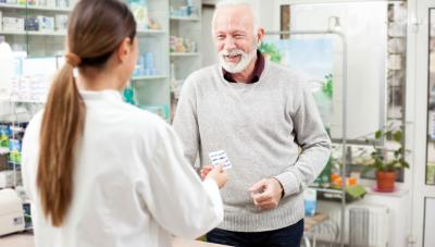 Man buying medication at pharmacy from pharmacist