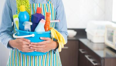 Woman's arms holding a bucket of cleaning supplies