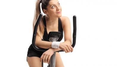 woman daydreaming while on exercise bike