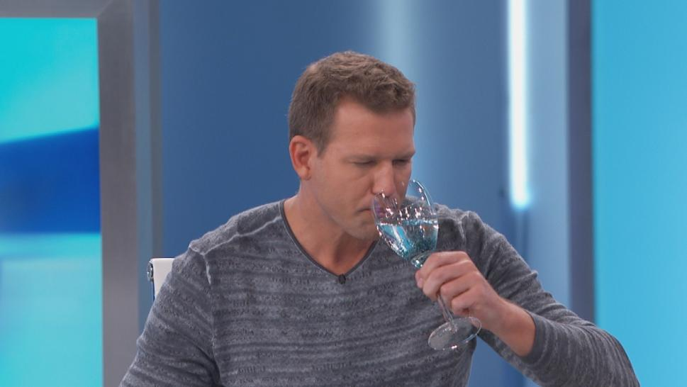 Dr. Travis drinks water out of a wine glass