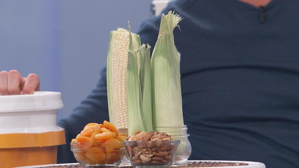 Corn on the cob, bowl of dried apricots, bowl of mixed nuts